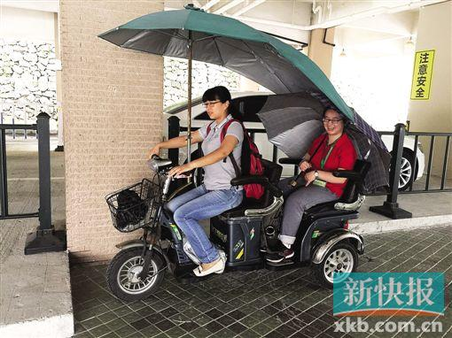 黄惠鹂骑着一辆电动小三轮车载着女儿穿梭在大学校园。