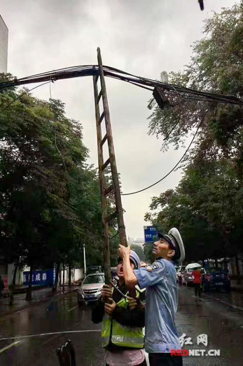 老交警雨中托举电缆一小时 浑身湿透
