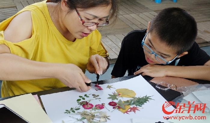 14个亲子家庭在园科院老师的指导下,学习压花,用干花制作钥匙扣和贺卡