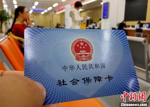 图为福州市市民服务中心前来办理社保业务的民众展示自己的社会保障卡。(资料图片)<a target='_blank' href='http://www.chinanews.com/' _fcksavedurl='http://www.chinanews.com/'></table><p align=