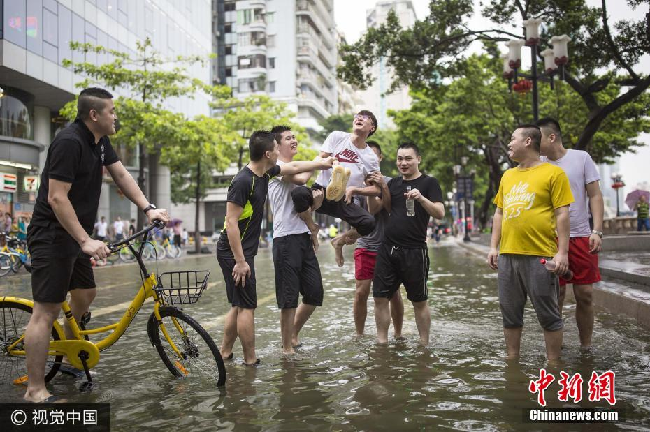 台风来袭珠江水倒灌 广州市民街头嬉戏捞鱼乐趣十足