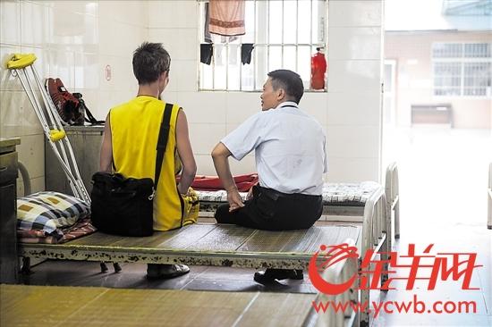 张齐辉(右)在救助站里与流浪人员谈心