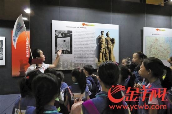 7月27日下午,广州的小学生们在讲解员的带领下参观《红旗飘飘——中国共产党党旗诞生历程珍贵档案展》