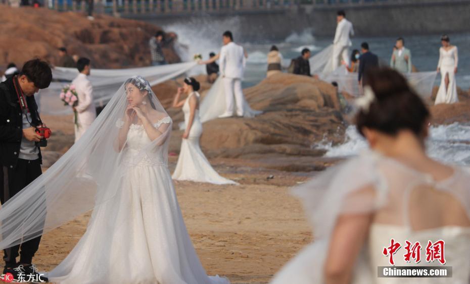 新人扎堆海水浴场拍婚纱照 放眼望去全是白纱