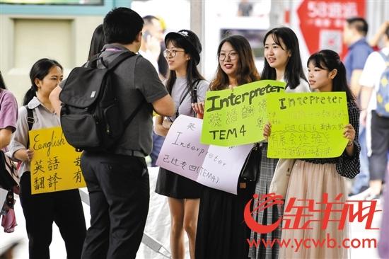 4月13日,大学生们举着手中的彩色牌子在广交会展馆门前应聘翻译