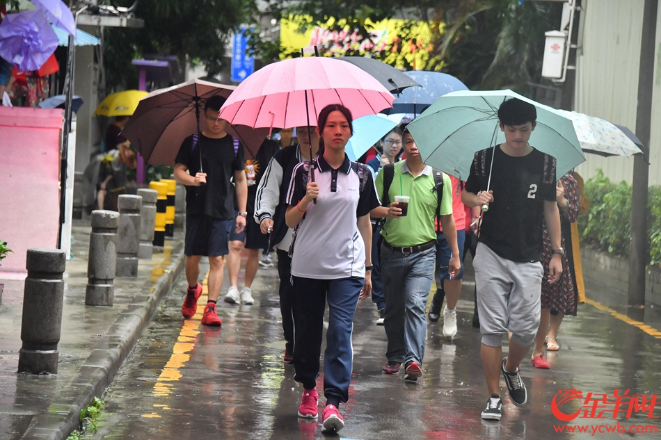 2018年6月7日,广州橙色暴雨预警下,21中考场参加高考的考生在家长、老师的祝福下从容淡定的进入考场。记者 黄巍俊 摄