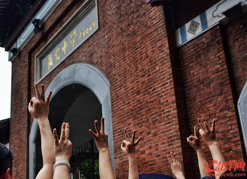 高考首日,广州大雨,在执信中学考点,大门外,家长在雨中盯着大门内等待。 记者 邓勃 摄影