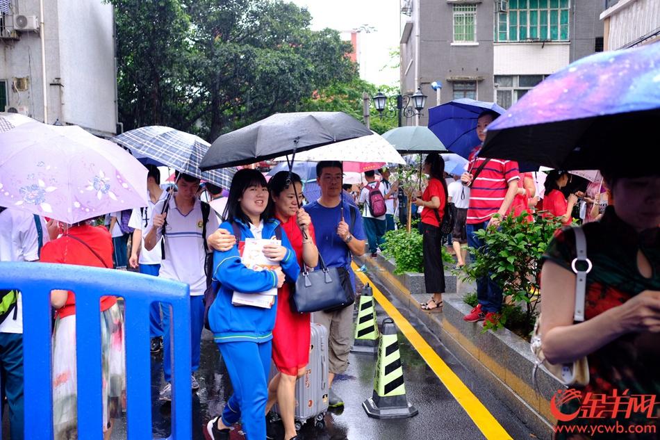 """今日高考,广州大雨,在广雅中学考点,送考的家长穿起红衣、旗袍,希望考生""""开门红、旗开得胜""""。记者 陈秋明 摄"""