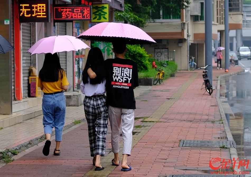 情人雨中浪漫散步。记者 陈秋明 摄