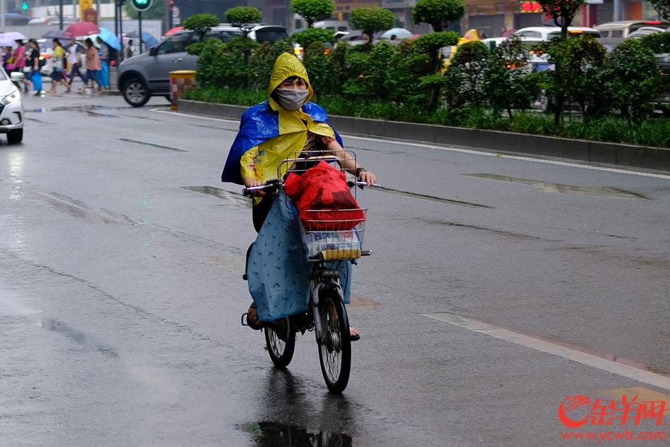 """市民""""全副武装""""应对下雨。记者 陈秋明 摄"""