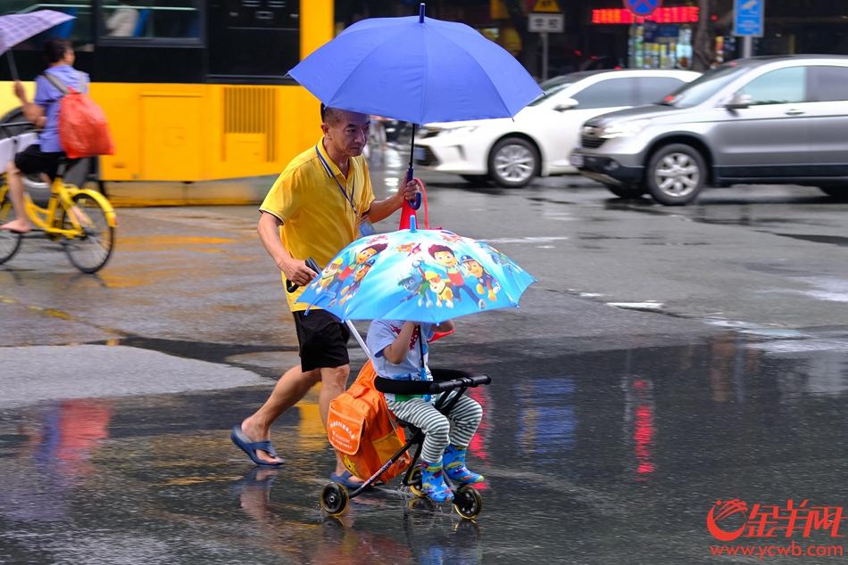 孩童上学也有卡通花伞准备。记者 陈秋明 摄