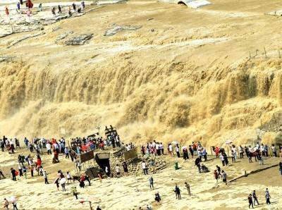 黄河壶口瀑布水量增大瀑布成群 游人显得很渺小