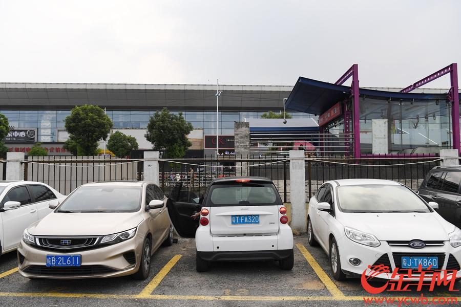 """2018年8月5日,广州""""开四停四""""限行政策开罚第一天,在""""开四停四""""禁行区外的厦滘地铁站旁的露天停车场里停有不少外地车辆。据停车场管理人员介绍,因为""""开四停四"""",最近这几天特别是今天(5日)来这里停放的外地车数量比以往多了很多。 该停车场收费最高为24元一天(24小时),不设月保。外地车车主王小姐表示""""这里停车不贵,停4天还不到100块,限行这几天先停这里,以后还是得抓紧摇号搞个广州牌。"""" 金羊网记者 周巍 摄影报道"""