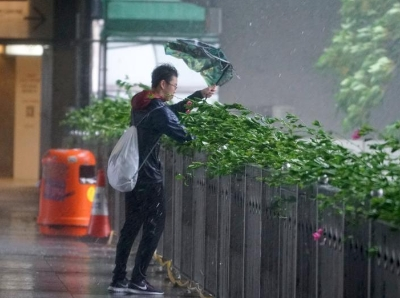 """香港受到""""山竹""""袭击 市民出行雨伞吹变形"""