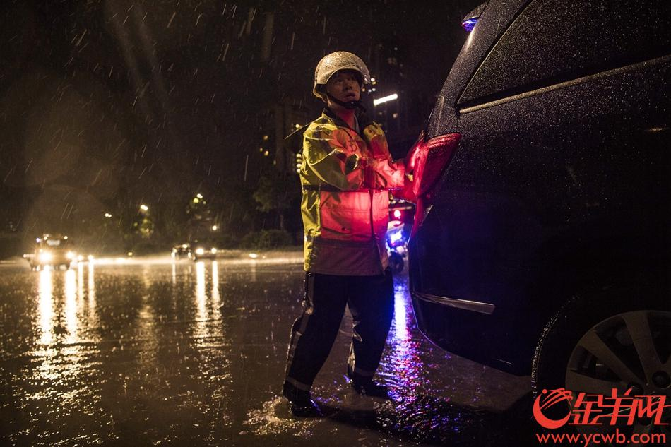 2018年9月16日晚23时许,广州交警执勤民警在广州大道中将一辆遭水浸死火的车辆推至安全区域。 记者 周巍 摄