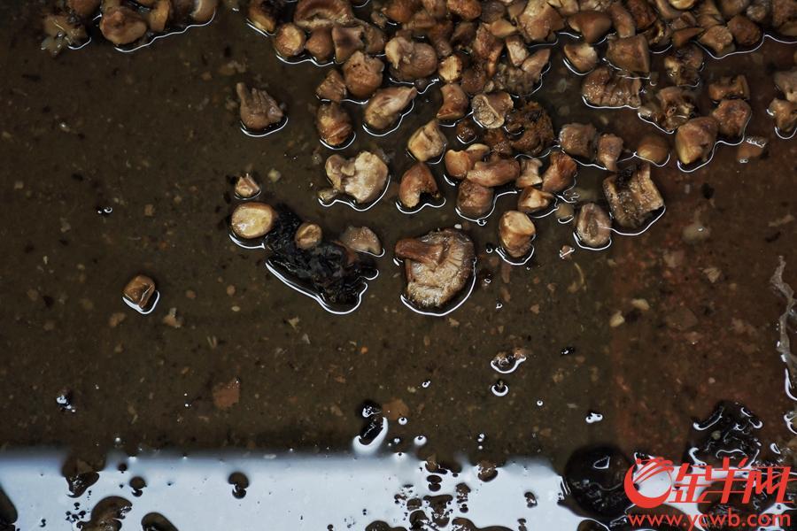 """受前兩日臺風山竹影響,廣州市一德路附近的潮音橫街(俗稱""""冬菇街"""")水浸嚴重,街上商鋪無一幸免,水浸最深達一米,擺放在低處的冬菇,木耳等幹貨均被泡濕。臺風過境後,水開始慢慢退去,從昨日開始商家們已經在清理受災貨品,直到今日(18日)下午17時仍有大量貨物沒有清理完。因水浸時間較長,受潮貨物堆積成山,本身就狹窄的""""冬菇街""""在廢棄幹貨的擠壓下更顯逼仄。在冬菇街賣了20多年幹貨的黃先生表示,這次各家的經濟損失估計有一百多萬元,大家正忙著清理貨物,現在就希望有關部門可以幫助清理一下街道裏的廢棄貨物,""""只有條街通順了,我們才能快點清理完,也方便開市迎客做生意啦!""""圖為  """"冬菇街""""仍然堆積了不少泡過水的貨物,工人們正忙著將成箱的廢棄貨物運出街道。 金羊網記者 周巍 攝"""