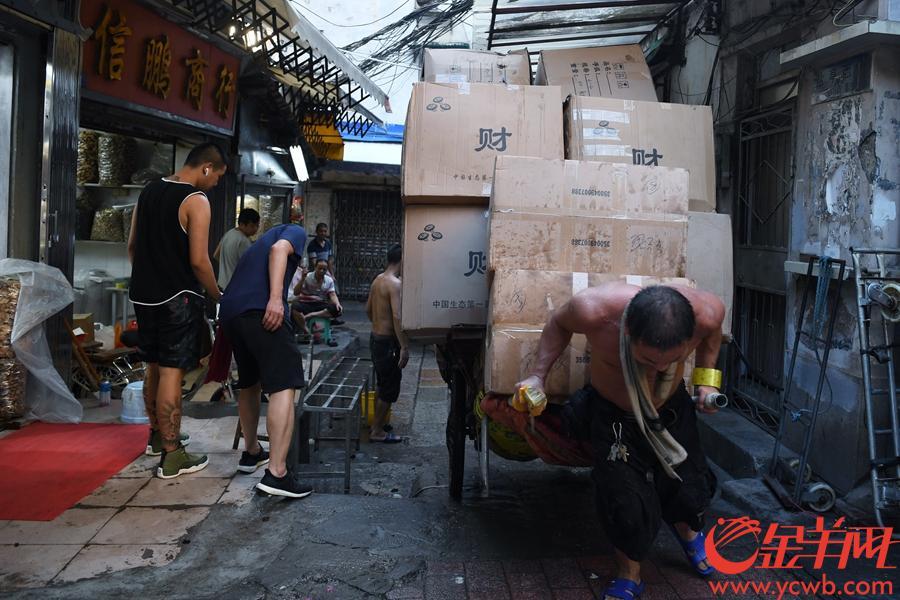 """受前两日台风山竹影响,广州市一德路附近的潮音横街(俗称""""冬菇街"""")水浸严重,街上商铺无一幸免,水浸最深达一米,摆放在低处的冬菇,木耳等干货均被泡湿。台风过境后,水开始慢慢退去,从昨日开始商家们已经在清理受灾货品,直到今日(18日)下午17时仍有大量货物没有清理完。因水浸时间较长,受潮货物堆积成山,本身就狭窄的""""冬菇街""""在废弃干货的挤压下更显逼仄。在冬菇街卖了20多年干货的黄先生表示,这次各家的经济损失估计有一百多万元,大家正忙着清理货物,现在就希望有关部门可以帮助清理一下街道里的废弃货物,""""只有条街通顺了,我们才能快点清理完,也方便开市迎客做生意啦!""""图为  """"冬菇街""""仍然堆积了不少泡过水的货物,工人们正忙着将成箱的废弃货物运出街道。 金羊网记者 周巍 摄"""