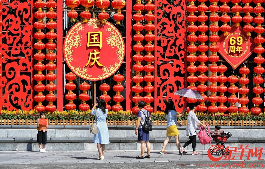 2018年是10月3日,国庆长假第三天,广州花城广场节日气氛十足,游人们在具有国庆特色的装饰背景前合影留念,庆祝伟大祖国69周岁华诞。  金羊网记者  汤铭明 摄影报道