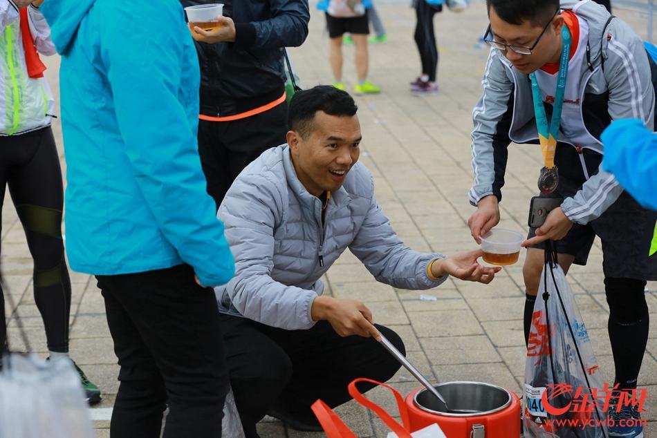 2018广州马拉松 ,在半程马拉松的终点,热心跑团组织免费为选手提供热姜汤取暖。 记者 宋金峪 摄