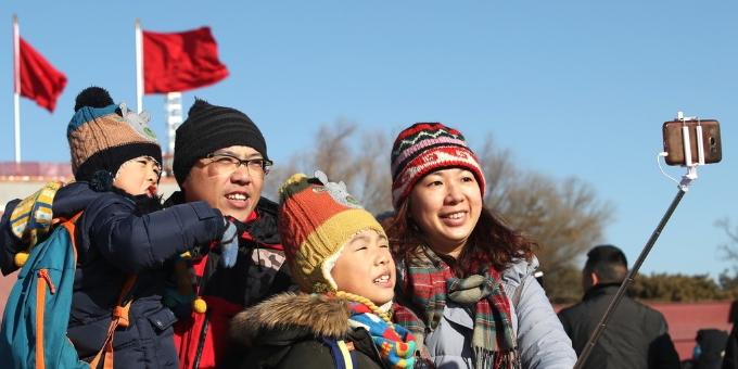北京冷空气来袭 游客裹得严实游览天安门热情不减