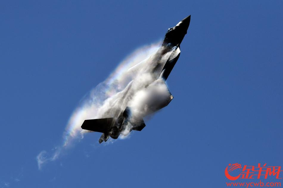 2018年11月6日,歼-20亮相珠海航展开幕式。歼-20进行飞行表演时,机翼产生的脱体涡上出现了一条彩虹。 金羊网记者 林桂炎 摄