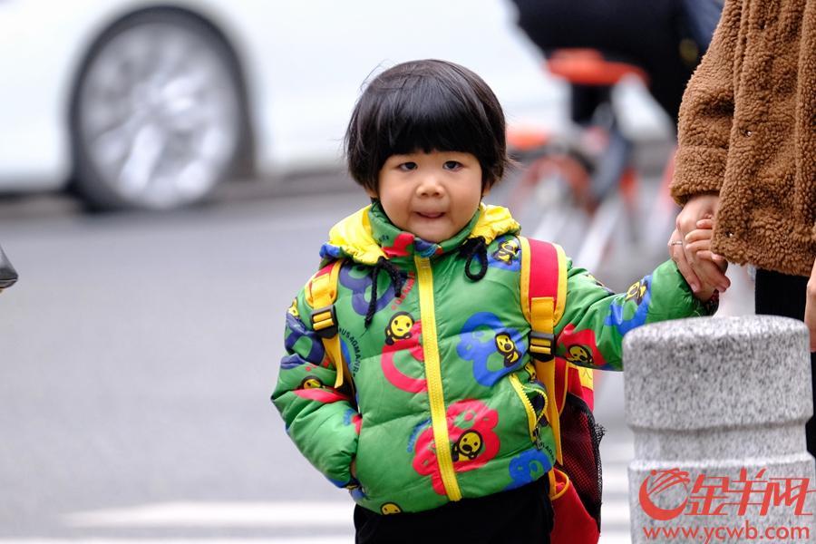 """1月16日,受冷空气影响,广州街头降温明显,荔湾区只有13度,出门的街坊大多添衣保暖,上学的孩童都""""包裹严实"""",但也有爱美的""""小姐姐""""依然短裙。金羊网记者  陈秋明 摄"""