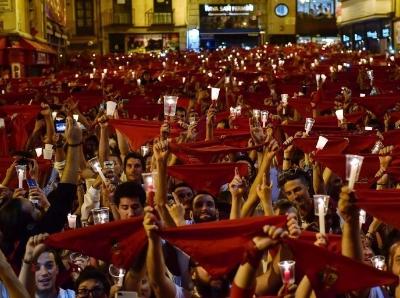 西班牙狂欢者高举红围巾和蜡烛唱歌庆祝奔牛节结束