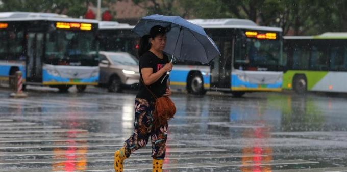 北京发布暴雨蓝色预警 民众冒雨出行