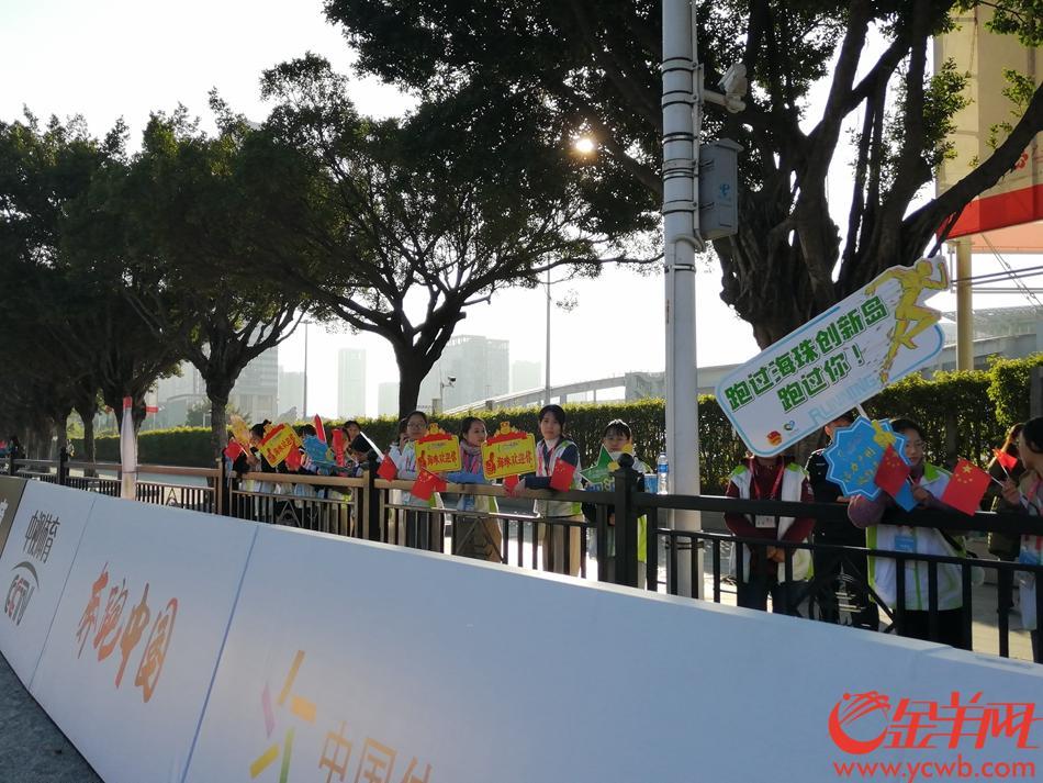 在琶洲半马赛道冲刺处,有许多志愿者已经举着小红旗、加油棒及加油广告牌等待跑者到来。原来他们是海珠区的志愿者们,他告诉记者,在这一赛段的志愿者就有300余人。(柳卓楠)
