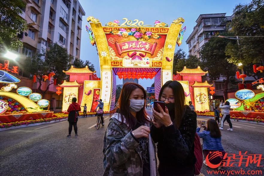 2020年1月21日,廣州市海珠區花市亮燈,不少市民嘗鮮在主牌坊拍照留影,亦有市民戴著口罩逛花市。 金羊網記者 宋金峪 攝