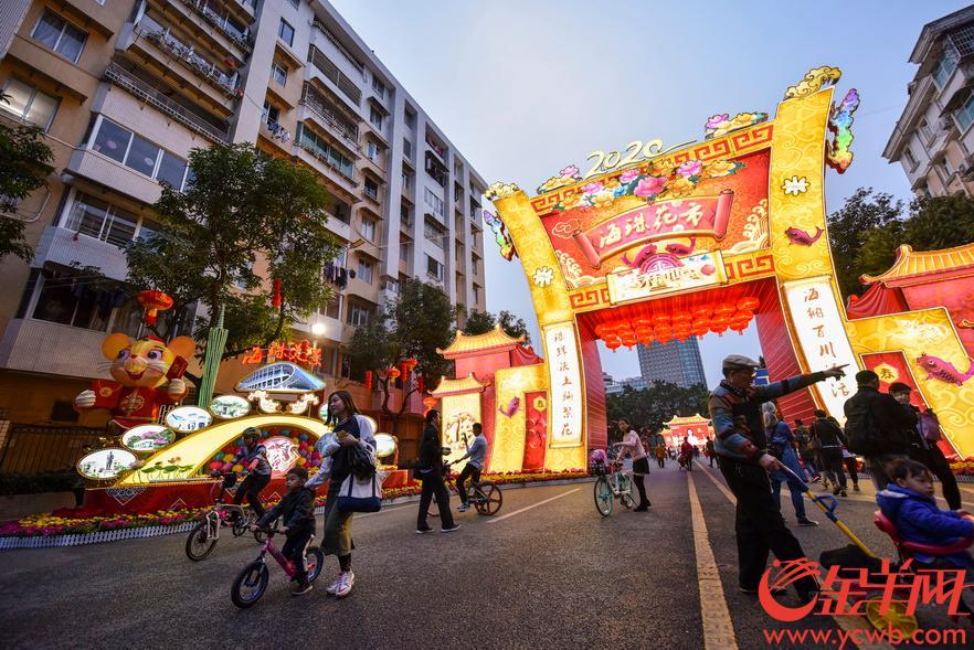 2020年1月21日,广州市海珠区花市亮灯,不少市民尝鲜在主牌坊拍照留影,亦有市民戴着口罩逛花市。 金羊网记者 宋金峪 摄