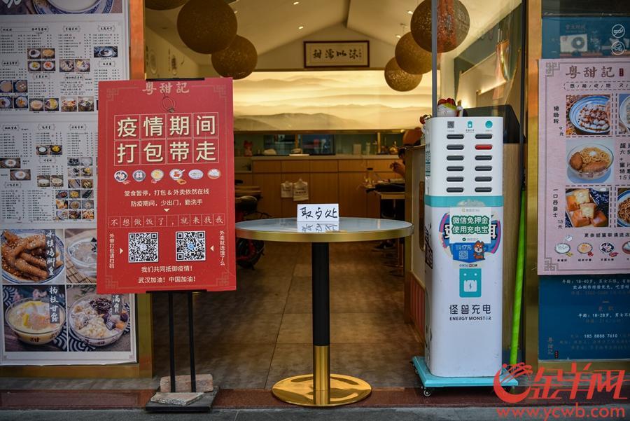 2020年2月12日,为进一步强化餐饮服务单位疫情防控有关措施,广州多区实施所有社会餐饮服务单位(含饮品店、小吃店、早餐店等,下同)暂停堂食服务,可提供到店自取、外卖订餐服务政策。图为海珠区艺苑南路,平时热闹的食街显得冷冷清清,不少饮食店铺仍未营业,三三两两的外卖小哥在路边等候取餐。沙龙国际网站记者 宋金峪 摄影报道