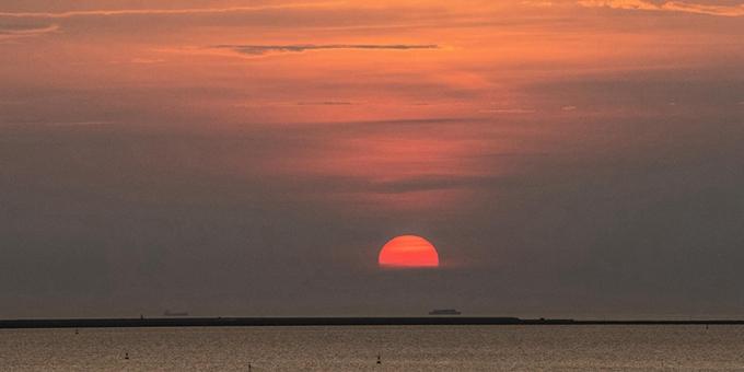落日余晖映海口