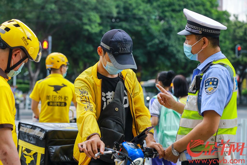 """2020年5月14日下午,广东省公安厅交通管理局在广州举办了""""一盔一带 安全常在""""警企联合劝导外卖骑手佩戴安全头盔活动启动仪式。启动仪式后,广州交警和外卖小哥一起在公园前地铁站外的劝导点,对上路不戴安全头盔的外卖员进行劝导。 羊城晚报全媒体记者 宋金峪 摄"""