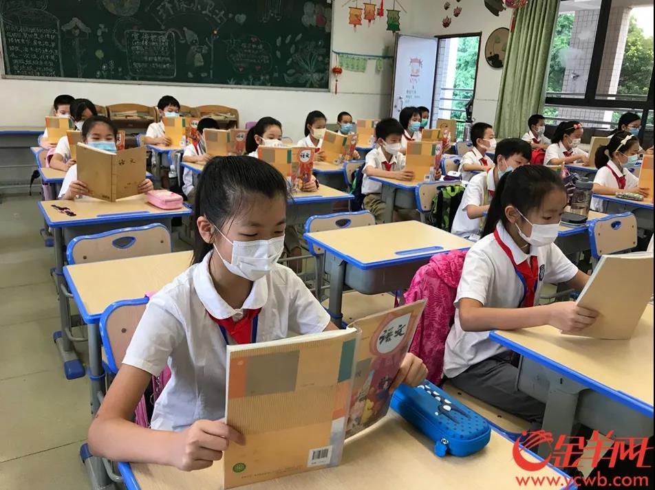 在华师附小,学校实行分批返校,目前所有学生已经到校完毕,正在教室里认真朗读课文。 羊城晚报全媒体记者 陈亮 摄