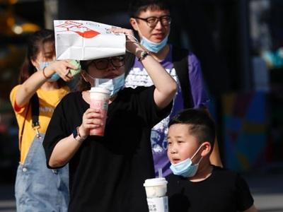北京高温再破纪录 市民遮阳出行