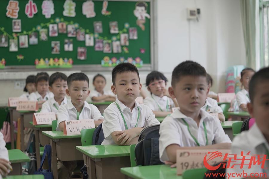 """2020年9月1日,广州中小学如期开学。东风东小学锦城校区举行了开学典礼,对低年级学生进行开笔礼。 学生们还领到了""""光盘""""冰箱贴。人人都做""""传递文明,拒绝浪费的代言人"""" 羊城晚报全媒体记者 林桂炎 实习生 袁咏珊 摄"""