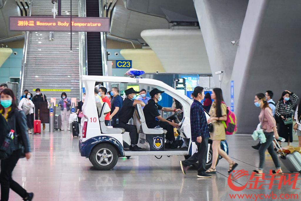 """2020年10月6日,国庆中秋假期已接近尾声,但是在广州市的各大景点和交通站点内,安保执勤人员依然没有松懈。广州塔下,执勤辅警们多人一组在地铁出入口维持秩序,他们疏导人流,手持喇叭播放""""这里是地铁通道,请不要在此逗留,谢谢配合""""""""请不要在通道口停留,注意脚下安全""""等安全警示公告;在广州南站,安保人员们在进站口站岗执勤、在站内开车巡逻,帮助旅客解决问题、保卫站内安全。 羊城晚报全媒体记者 梁喻 摄"""