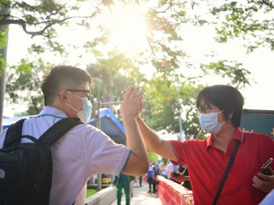 广州高考考生有序进入考场 与老师击掌打气