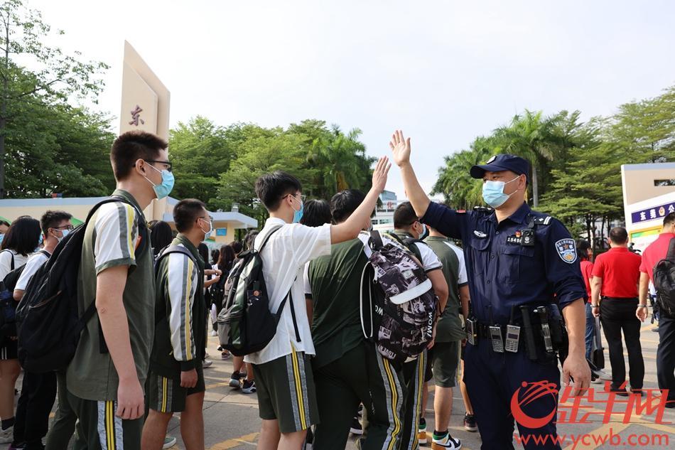 2021年6月7日,高考启幕。东莞考生进考点前,执勤警察给考生鼓劲。羊城晚报全媒体记者 王俊伟 摄