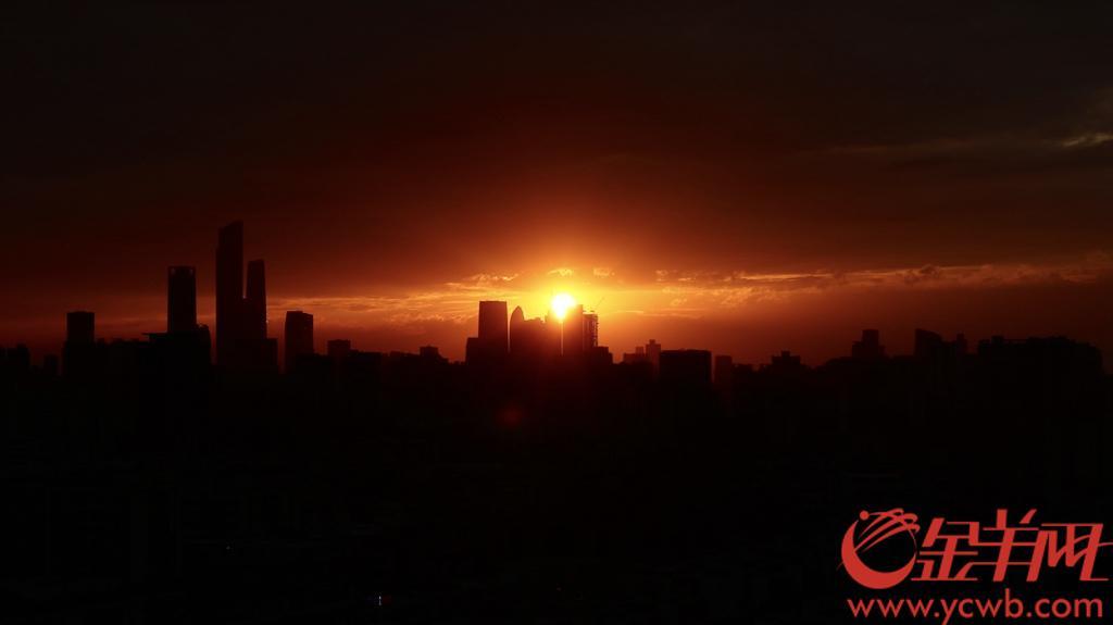 """10月7日,国庆假期最后一天。广州一轮被乌云遮挡的落日,在沉入地平线前微微探了个头,出现在云与高楼之间,宛如""""天地之眼"""",给国庆假期画上完美句号。图/羊城晚报全媒体记者 曾育文"""